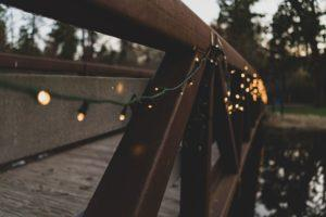 wooden bridge with warm white led light string strung on rail